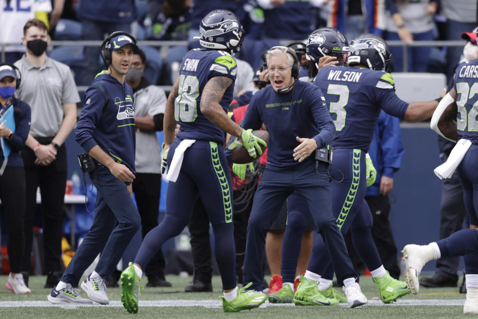 Seattle Seahawks head coach Pete Carroll, center, and his son, wide receivers coach Nate Carroll, left, greet wide receiver Freddie Swain after Swain scored a touchdown against the Tennessee Titans during the second half of an NFL football game, Sunday, Sept. 19, 2021, in Seattle. (AP Photo/John Froschauer)