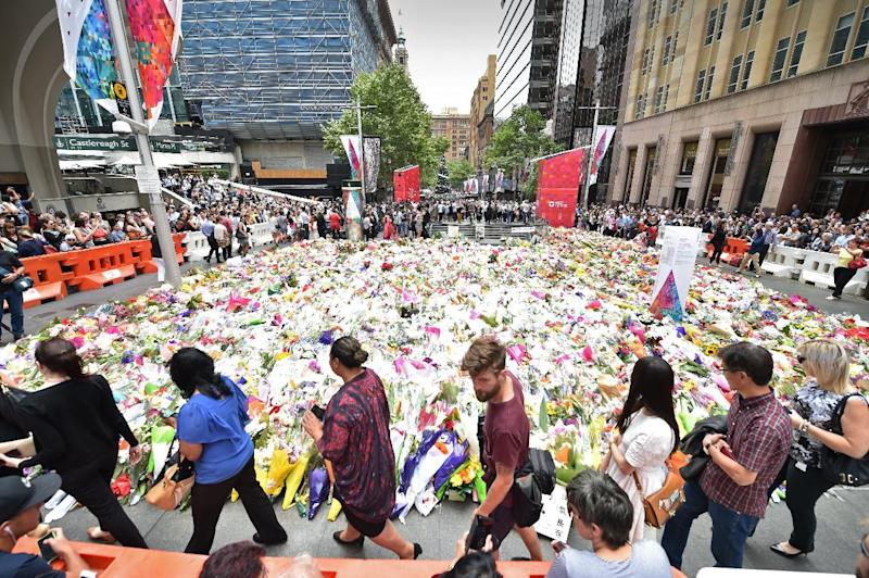 Visitors walk past flowers at a makeshift memorial near the scene of a fatal siege in the heart of Sydney's financial district on December 17, 2014 (AFP Photo/Peter Parks)