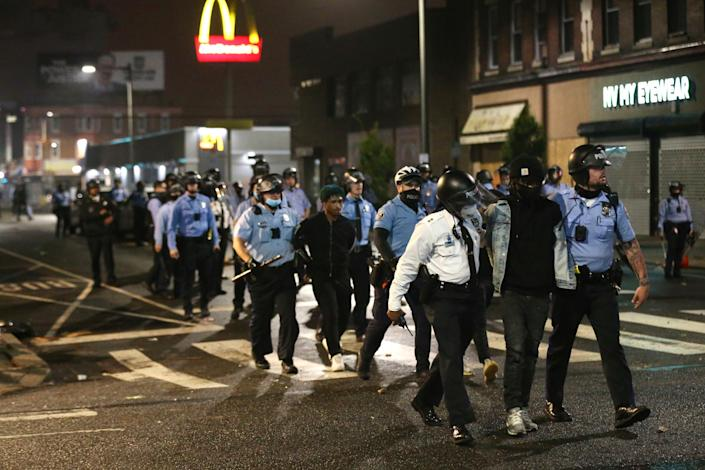 Police lead several people in handcuffs to a police van on 52nd Street in West Philadelphia in the early hours of Tuesday.