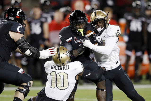"Michael Warren II #3 of the <a class=""link rapid-noclick-resp"" href=""/ncaaf/teams/cincinnati/"" data-ylk=""slk:Cincinnati Bearcats"">Cincinnati Bearcats</a> gets tackled by Nate Evans #44 and Eriq Gilyard #10 of the Central Florida Knights in the first quarter. (Getty)"