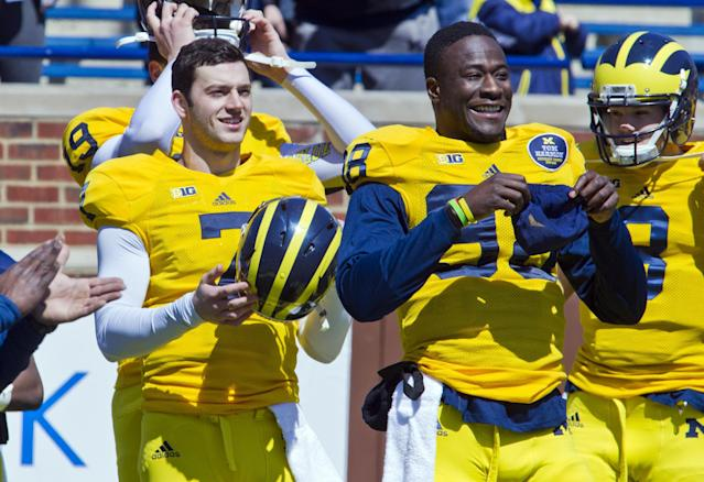 Michigan quarterback Shane Morris, front left, and quarterback Devin Gardner, front right, laugh as they put on equipment for the football team's annual spring football game on Saturday, April 5, 2014, in Ann Arbor, Mich. (AP Photo/Tony Ding)