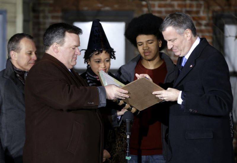 City Clerk Michael McSweeney, second from left, assists Bill de Blasio, right, as he signs the oath of office while from left, State Attorney General Eric Schneiderman, Chiara de Blasio and Dante de Blasio look on Wednesday, Jan. 1, 2014 in New York. De Blasio took the oath of office moments after midnight at his home in Park Slope, Brooklyn, his inauguration will be celebrated at noon Wednesday on the steps of City Hall when he takes the oath again, which will be administered by former President Bill Clinton.(AP Photo/Seth Wenig, Pool)