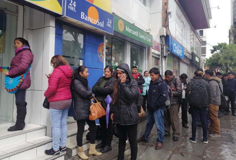 People line up to use cash machines, amid protests in La Paz, Bolivia, Monday, Nov. 11, 2019. The Nov. 10 resignation of President Evo Morales leaves a power vacuum and a country torn by protests against and for his government. ( (AP Photo/Paola Flores)