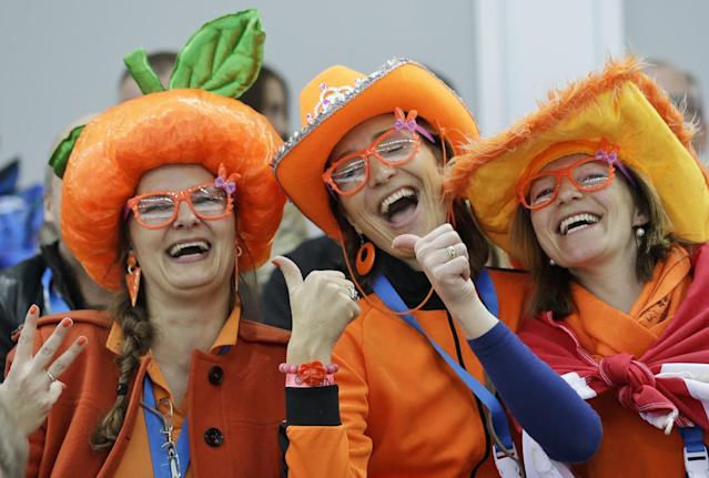 Dutch skating fans, one flashing three fingers presumably for country skater Sven Kramer's projected three gold medals, cheer during the men's 5,000-meter speedskating race at the Adler Arena Skating Center during the 2014 Winter Olympics, Saturday, Feb. 8, 2014, in Sochi, Russia. (AP Photo/Patrick Semansky)