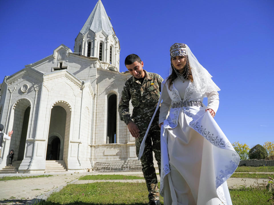 Newlyweds, soldier Hovhannes Hovsepyan, left, and Mariam Sargsyan walk after their wedding ceremony in the Holy Savior Cathedral, damaged by shelling by Azerbaijan's artillery during a military conflict in Shushi, the separatist region of Nagorno-Karabakh, Saturday, Oct. 24, 2020. The wedding was celebrated even as intense fighting in the region has continued. (AP Photo)