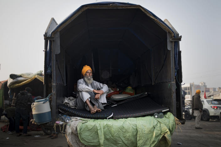Darshan Singh, 68, sits at the back of his tractor trailer parked on a highway, adding to a convoy of farmers' trucks, trailers and tractors sretching for at least three kilometers (1.8 miles), protesting against new farm laws, at the Delhi-Haryana state border, India, Tuesday, Dec. 1, 2020. The protests started in September but drew nationwide attention last week when the farmers marched from northern Punjab and Haryana, two of India's largest agricultural states. On their way to the capital, they pushed aside concrete barricades set up by police and braved tear gas, batons and water cannons. (AP Photo/Altaf Qadri)