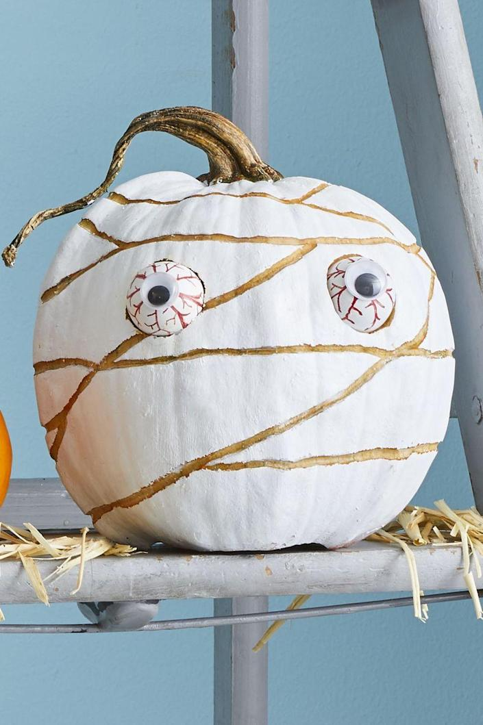 """<p>Start by painting your pumpkin completely white, then use a pen to freehand a mummy-style wrap design on it. Etch the lines using a linoleum-cutting tool. To create the eyes, glue googly eyes to two Ping-Pong balls and hand-draw red veins using a red Sharpie, then insert into two carved """"eye sockets.""""</p><p><a class=""""link rapid-noclick-resp"""" href=""""https://www.amazon.com/Speedball-4131-Linoleum-Assorted-Cutters/dp/B0017D8W5E?tag=syn-yahoo-20&ascsubtag=%5Bartid%7C10070.g.1902%5Bsrc%7Cyahoo-us"""" rel=""""nofollow noopener"""" target=""""_blank"""" data-ylk=""""slk:SHOP LINOLEUM CUTTERS"""">SHOP LINOLEUM CUTTERS</a> </p>"""