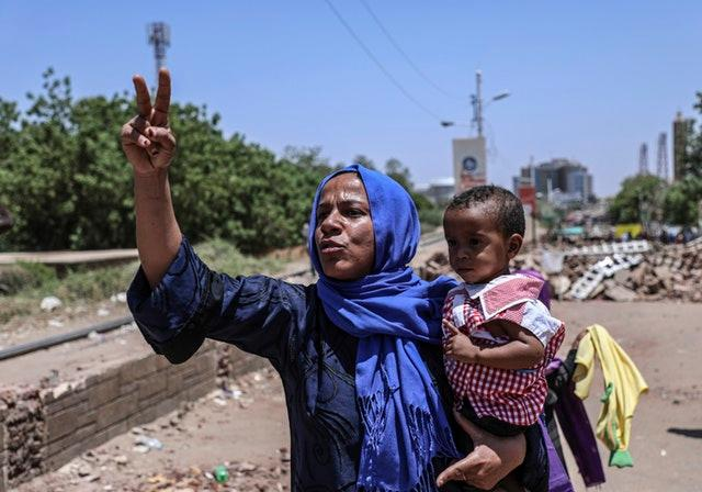 A protester holding her child in a street leading to the sit-in outside the military headquarters in Khartoum