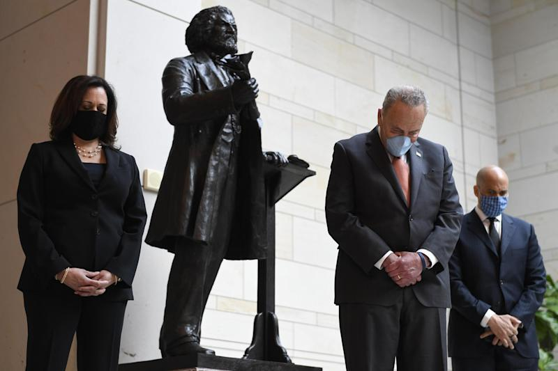 Standing near a statue of Frederick Douglass, Senator Kamala Harris, left, Senate Minority Leader Chuck Schumer, centre, and Senator Cory Booker, right, pause during a prayer on Capitol Hill on Thursday: AP Photo/Susan Walsh