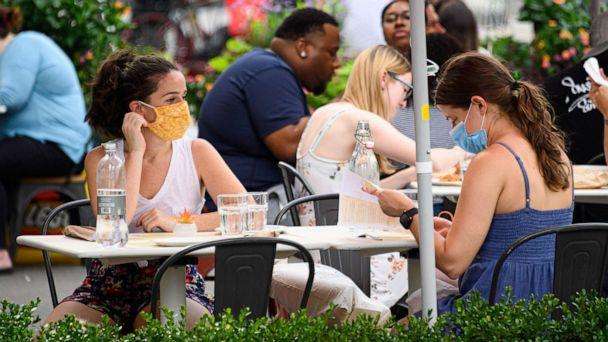 PHOTO: People wear protective face masks at an outdoor restaurant in the Flatiron District of New York, July 26, 2020. (Noam Galai/Getty Images)