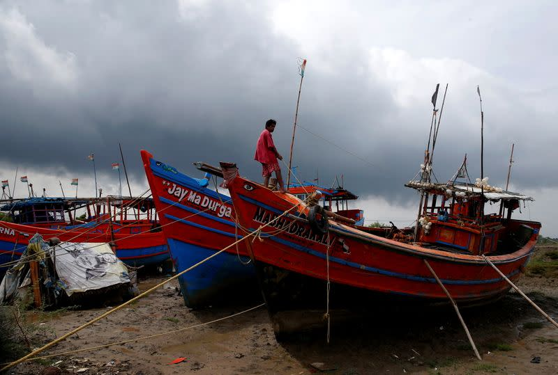 A fisherman ties his boat on a shore ahead of Cyclone Yaas in Digha