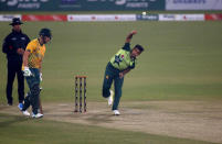Pakistan's Zahid Mahmood, right, bowls while South Africa's David Miller watches during the 3rd Twenty20 cricket match between Pakistan and South Africa at the Gaddafi Stadium, in Lahore, Pakistan, Sunday, Feb. 14, 2021. (AP Photo/K.M. Chaudary)