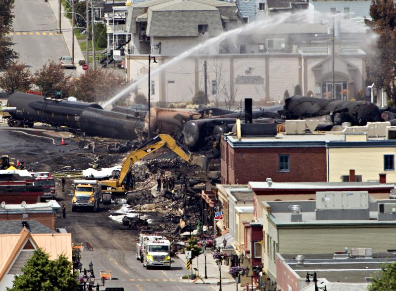 Searchers dig through the rubble for victims of the inferno in Lac-Megantic, Quebec, Monday, July 8, 2013, as firefighter continue to hose down tanker cars to prevent explosions. A runaway train derailed igniting tanker cars carrying crude oil early Saturday. (AP Photo/ THE CANADIAN PRESS,Ryan Remiorz)
