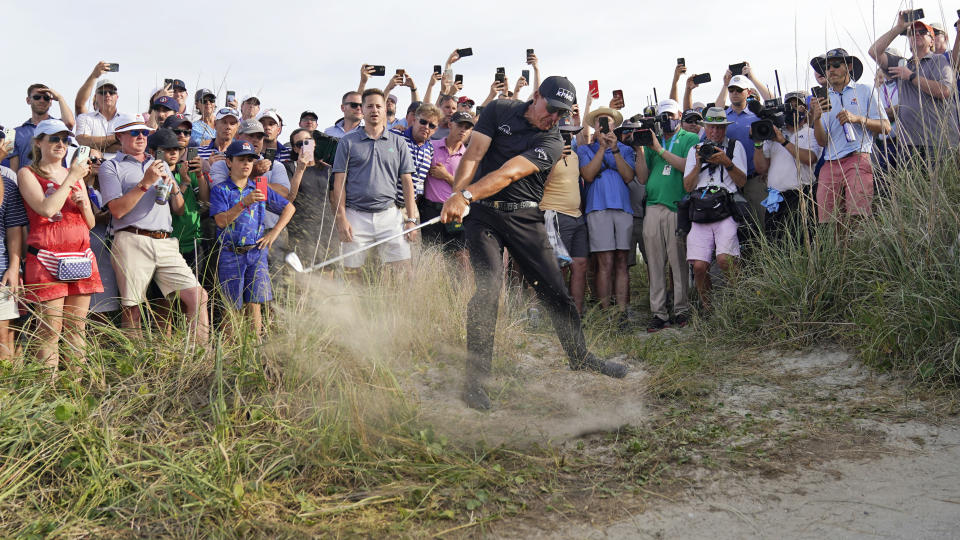 Phil Mickelson hits his second shot on the 16th hole from the rough during the third round at the PGA Championship golf tournament on the Ocean Course, Saturday, May 22, 2021, in Kiawah Island, S.C. (AP Photo/David J. Phillip)