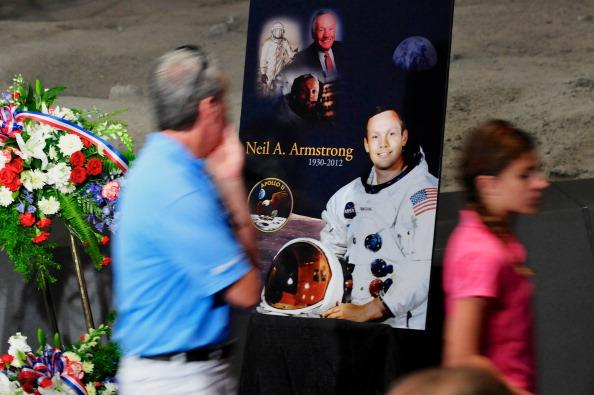Tourists pass a poster and flowers in honor of former NASA astronaut Neil Armstrong at the Apollo/Saturn V Center, August 31, 2012 in Cape Canaveral, Florida. Armstrong, the first man to walk on the moon, died from complications from heart surgery at the age of 82. (Photo by Roberto Gonzalez/Getty Images)