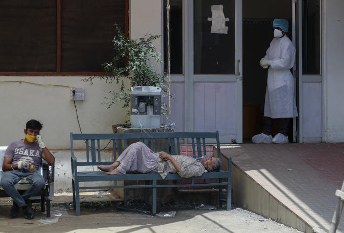 A COVID-19 patient receives oxygen outside a government run hospital in Jammu, India, Wednesday, May 19, 2021. India has the second-highest coronavirus caseload after the U.S. with more than 25 million confirmed infections.(AP Photo/Channi Anand)