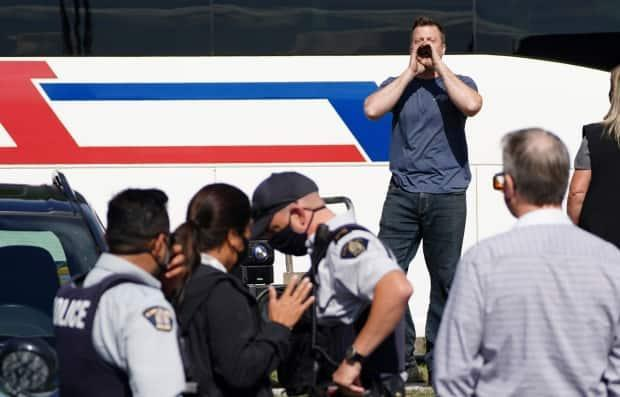 A lone protester heckles Liberal Leader Justin Trudeau as he takes part in an interview with Global reporter Neetu Garcha in Burnaby, B.C., on Monday. The interview was supposed to take place outside but had to be moved inside because of the protester.  (Sean Kilpatrick/Canadian Press - image credit)