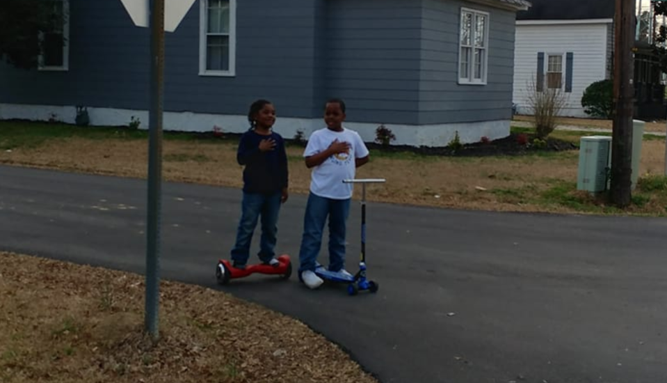 A moment captured by a chaplain is going viral. It shows two young people who stopped playing and said the Pledge of Allegiance as a flag was being raised at a fire department. (Photo: Facebook)