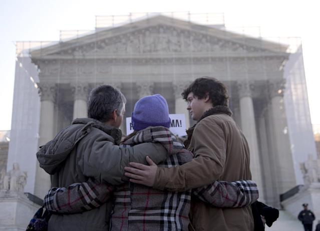 A group from Alabama prays in front of the Supreme Court in Washington, Wednesday, March 27, 2013, before the court's hearing on the Defense of Marriage Act (DOMA). In the second of back-to-back gay marriage case, the Supreme Court is turning to a constitutional challenge to the law that prevents legally married gay Americans from collecting federal benefits generally available to straight married couples. (AP Photo/Carolyn Kaster)
