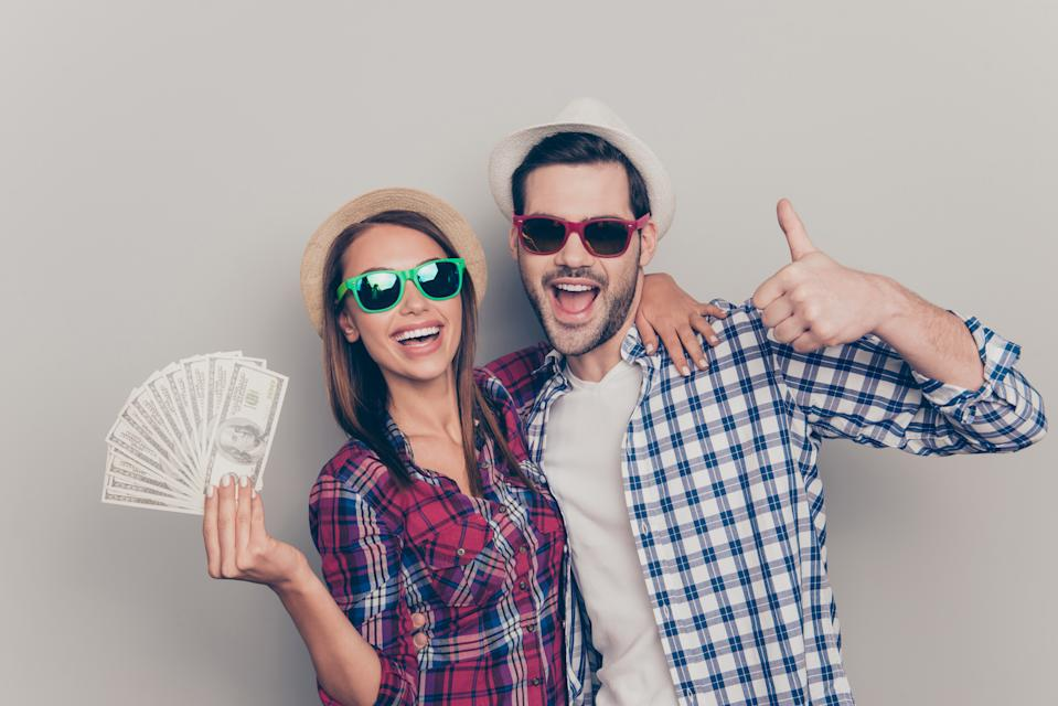 Portrait of two nice attractive cheerful people married spouses husband wife wearing eyeglasses eyewear checked shirt showing thumbup fan of hundreds usd isolated over gray pastel background