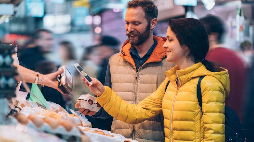 Smiling couple buying fresh eggs and paying contactless with smartphone.