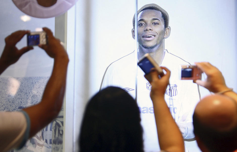 Fans take photographs of an image of Brazilian striker Robinho at the Santos soccer club trophy room in Santos February 1, 2010.  Robinho arrived in Brazil on Saturday to begin a six-month loan spell with Santos from English Premier League side Manchester City. The 26-year-old asked City for the loan move in a bid to improve his chances of making Brazil's 2010 World Cup squad after struggling in England. REUTERS/Alex Almeida (Brazil - Tags: SPORT SOCCER)
