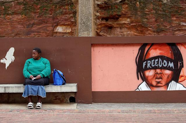 <p>A woman sits next to murals as opposition parties march for the removal of President Jacob Zuma outside the Constitutional Court in Johannesburg, South Africa, May 15, 2017. (Photo: Mike Hutchings/Reuters) </p>