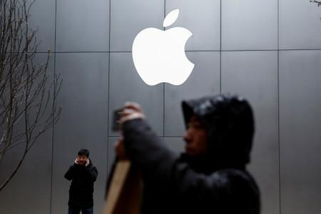 FILE PHOTO: People use their phones outside an Apple store in Beijing