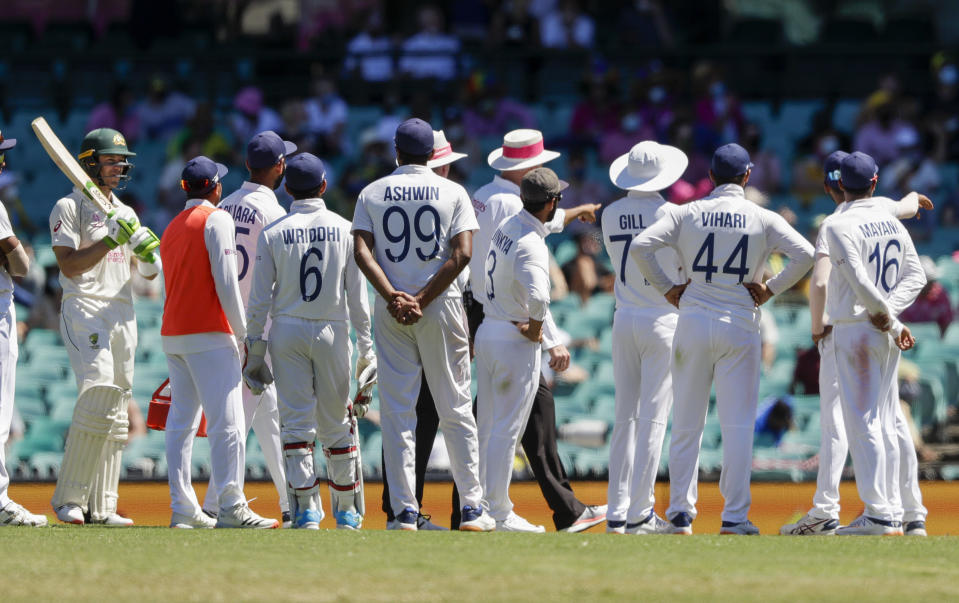 Australia's Tim Paine, left, waits as Indian players talk with the umpires over an issue with the crowd during play on day four of the third cricket test between India and Australia at the Sydney Cricket Ground, Sydney, Australia, Sunday, Jan. 10, 2021. (AP Photo/Rick Rycroft)