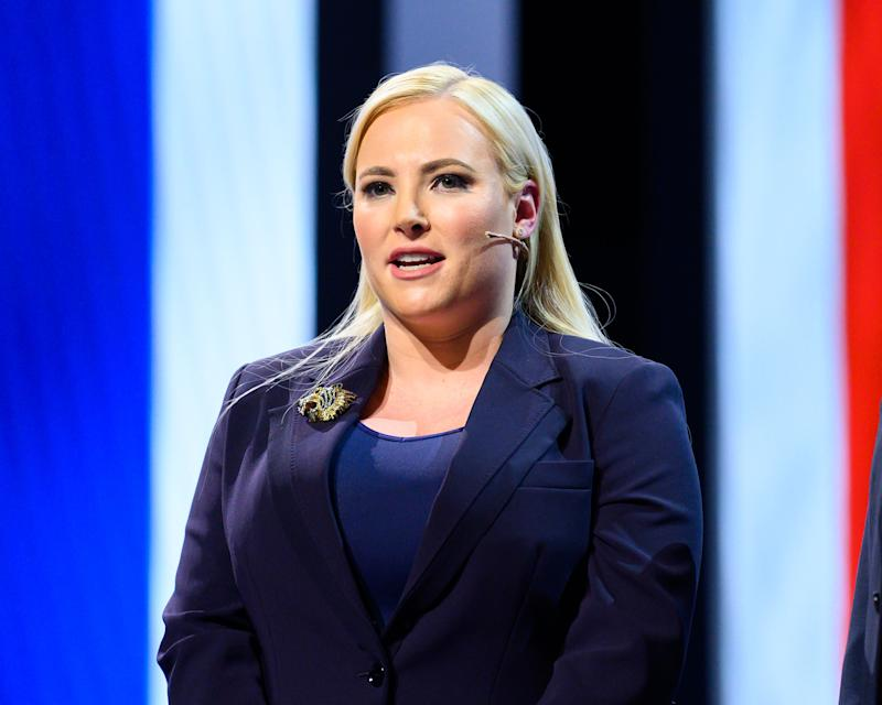 Meghan McCain stands n stage wearing a microphone