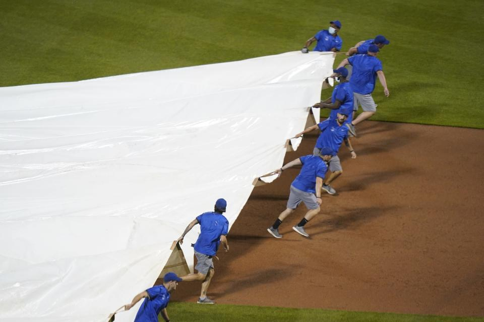 Grounds crew members cover the field as play is suspended due to rain during the eighth inning of a baseball game between the New York Mets and the Pittsburgh Pirates, Friday, July 9, 2021, in New York. (AP Photo/Frank Franklin II)