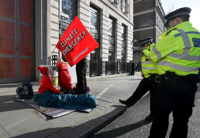 Greenpeace climate activists attempt to block the entrance to BP's head office in London