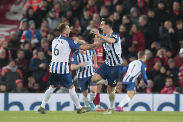 Brighton's Lewis Dunk, right, celebrates after scoring during the English Premier League soccer match between Liverpool and Brighton at Anfield Stadium, Liverpool, England, Saturday, Nov. 30, 2019. (AP Photo/Jon Super)
