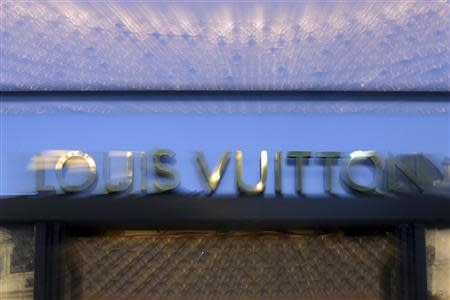A Louis Vuitton sign is seen at one of their Paris stores September 24, 2013. REUTERS/Philippe Wojazer