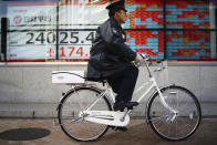 A police officer rides a bicycle past an electronic stock board showing Japan's Nikkei 225 index at a securities firm in Tokyo Tuesday, Jan. 14, 2020. Asian shares followed Wall Street higher on Tuesday amid optimism that a trade deal between the U.S. and China will be a boon for the regional economy. (AP Photo/Eugene Hoshiko)