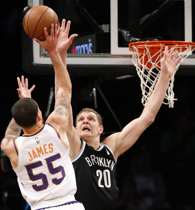 FILE - In this Oct. 31, 2017, file photo, Phoenix Suns guard Mike James (55) shoots as Brooklyn Nets center Timofey Mozgov (20) defends in the first half of an NBA basketball game, in New York. A person familiar with the situation says the Charlotte Hornets have agreed to trade eight-time All-Star center Dwight Howard to the Brooklyn Nets for center Timofey Mozgov and two future second-round draft picks. The person spoke to The Associated Press on condition of anonymity Wednesday, June 20, 2018, because the teams have not announced the trade and the league has not yet approved it. (AP Photo/Kathy Willens, File)