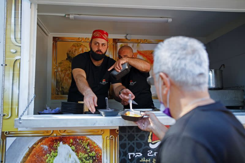 A man receives Kanafeh, a Middle Eastern dessert, after he was vaccinated against the coronavirus disease (COVID-19), as part of an initiative to encourage people to get vaccinated, near a mobile vaccination unit in Jaffa