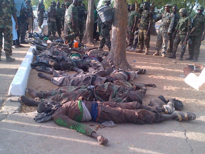 In this photo taken with a mobile phone, Tuesday, May. 7, 2013, soldiers looks at bodies of suspected Islamic extremist killed during heavy fighting in Bama, Nigeria. Coordinated attacks by Islamic extremists armed with heavy machine guns killed at least 42 people in northeast Nigeria, authorities said Tuesday, the latest in a string of increasingly bloody attacks threatening peace in Africa's most populous nation. The attack struck multiple locations in the hard-hit town of Bama in Nigeria's Borno state, where shootings and bombings have continued unstopped since an insurgency began there in 2010. Fighters raided a federal prison during their assault as well, freeing 105 inmates in another mass prison break to hit the country, officials said. (AP Photo/Abdukareem Haruna)
