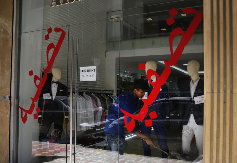 "In this Thursday, July 18, 2019 photo, a worker cleans a display in shop with Arabic on the window that read: ""Liquidation"" and ""the shop is for rent,"" in Hamra street, Beirut, Lebanon. As the economic crisis deepens in Lebanon, so has the public's distrust in the ability of the old political class, widely viewed as corrupt and steeped in personal rivalries, to tackle major reform. Many fear a Greek-style bankruptcy, without the European Union to fall back on, and with a potentially more violent social unrest in the small country wedged between war-torn Syria and Israel. (AP Photo/Hussein Malla)"