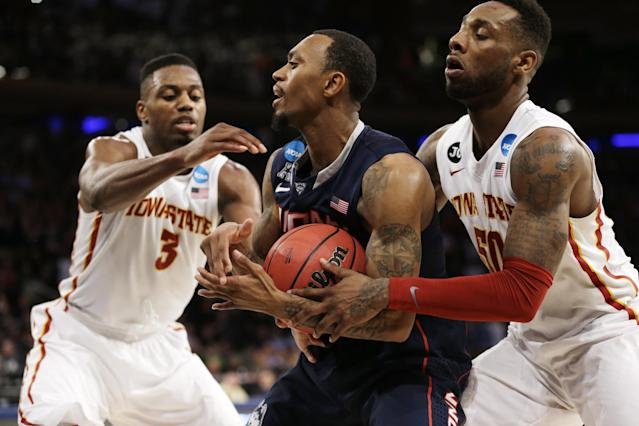 Connecticut's Ryan Boatright, center, struggles to hold the ball while covered by Iowa State's Melvin Ejim, left, and DeAndre Kane during the second half in a regional semifinal of the NCAA men's college basketball tournament Friday, March 28, 2014, in New York. Connecticut won 81-76. (AP Photo/Seth Wenig)