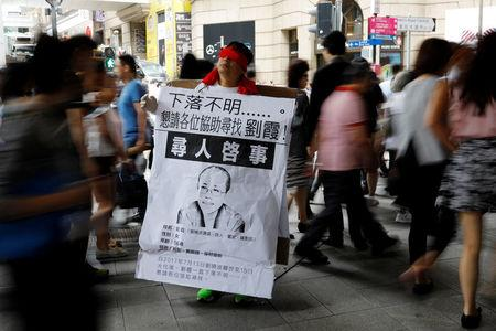 """A protester covers his eyes with red ribbon to call for the release of late Chinese Nobel Peace Prize laureate Liu Xiaobo's wife Liu Xia, in Hong Kong, China August 16, 2017. The banner reads """"Missing person. Please help to find Liu Xia."""" REUTERS/Tyrone Siu"""
