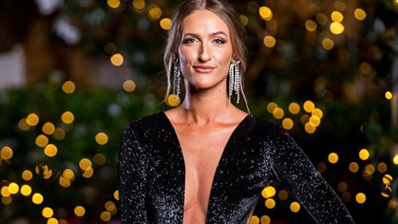 A photo of The Bachelor Australia contestant Isabelle Davies wearing a black dress on set in episode four.