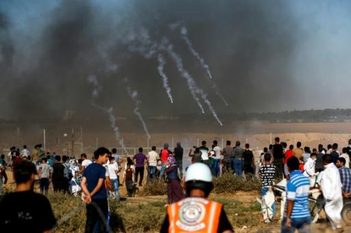A picture taken on July 20, 2018 shows tear gas canisters fired by Israeli forces landing among protesters along the border with Israel east of Khan Yunis in the southern Gaza Strip