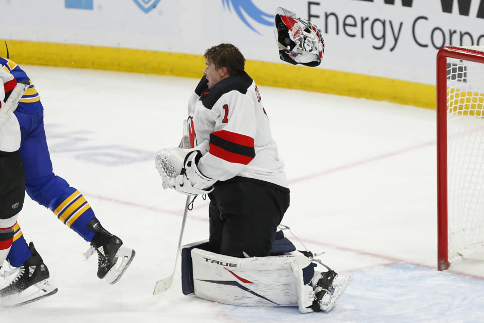New Jersey Devils goalie Eric Comrie (1) loses his mask during the third period of an NHL hockey game against the Buffalo Sabres, Sunday, Jan. 31, 2021, in Buffalo, N.Y. (AP Photo/Jeffrey T. Barnes)