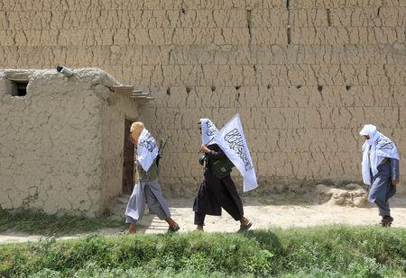 Taliban walk as they celebrate ceasefire in Ghani Khel district of Nangarhar province, Afghanistan