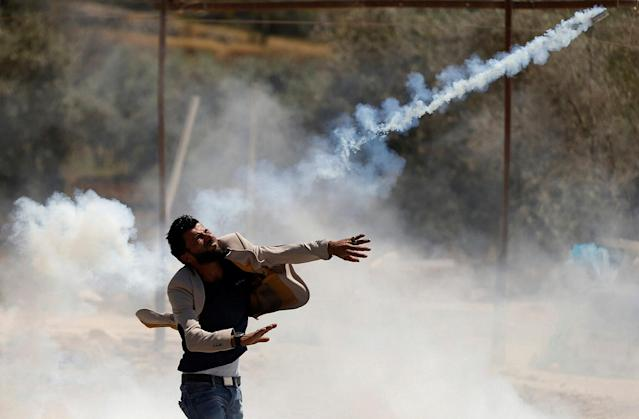 <p>A Palestinian protester hurls back a tear gas canister fired by Israeli troops during clashes in the West Bank village of Beita, near Nablus on May 12, 2017. (Photo: Mohamad Torokman/Reuters) </p>