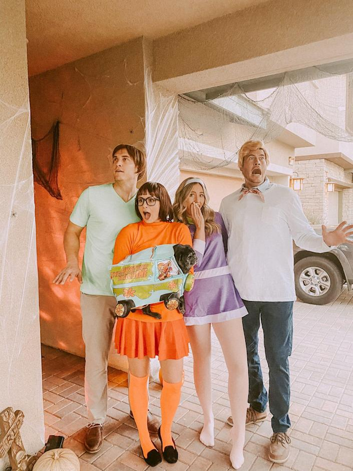 """A group of four dressed as Shaggy, Velma, Daphne, and Fred from """"Scooby Doo"""" pose for a photo."""