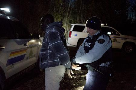 "A man who claimed to be from Sudan who kept saying ""I just want to be safe"" is handcuffed by a Royal Canadian Mounted Police (RCMP) officer after he illegally crossed the U.S.-Canada border leading into Hemmingford, Quebec, Canada, March 20, 2017. REUTERS/Christinne Muschi"