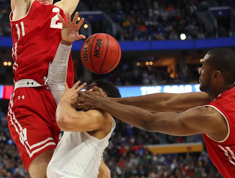 <p>Villanova guard Josh Hart (3) drives to the basket against Wisconsin forward Ethan Happ (22) and forward Vitto Brown (30) with three seconds remaining in the second half of a second-round men's college basketball game in the NCAA Tournament, Saturday, March 18, 2017, in Buffalo, N.Y. A Villanova foul was called on the play and Wisconsin won, 65-62. (AP Photo/Bill Wippert) </p>