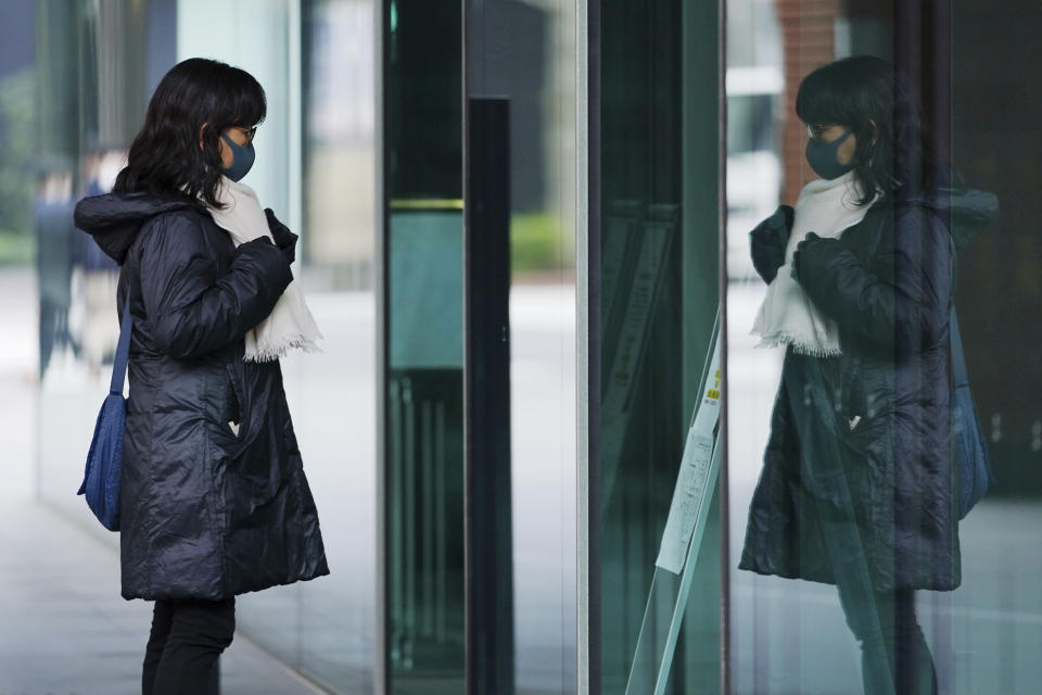 A woman wearing a face mask to help curb the spread of the coronavirus adjusts her scarf in her reflection on a window Friday, Feb. 26, 2021, in Tokyo. The Japanese capital confirmed more than 270 new coronavirus cases on Friday. (AP Photo/Eugene Hoshiko)